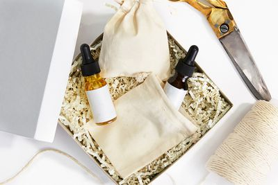 A cardboard box with two glass bottles and canvas bag sit on white background Surrounded by other objects
