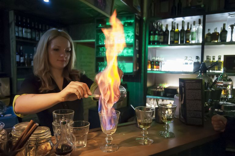 A bartender lighting a drink on fire