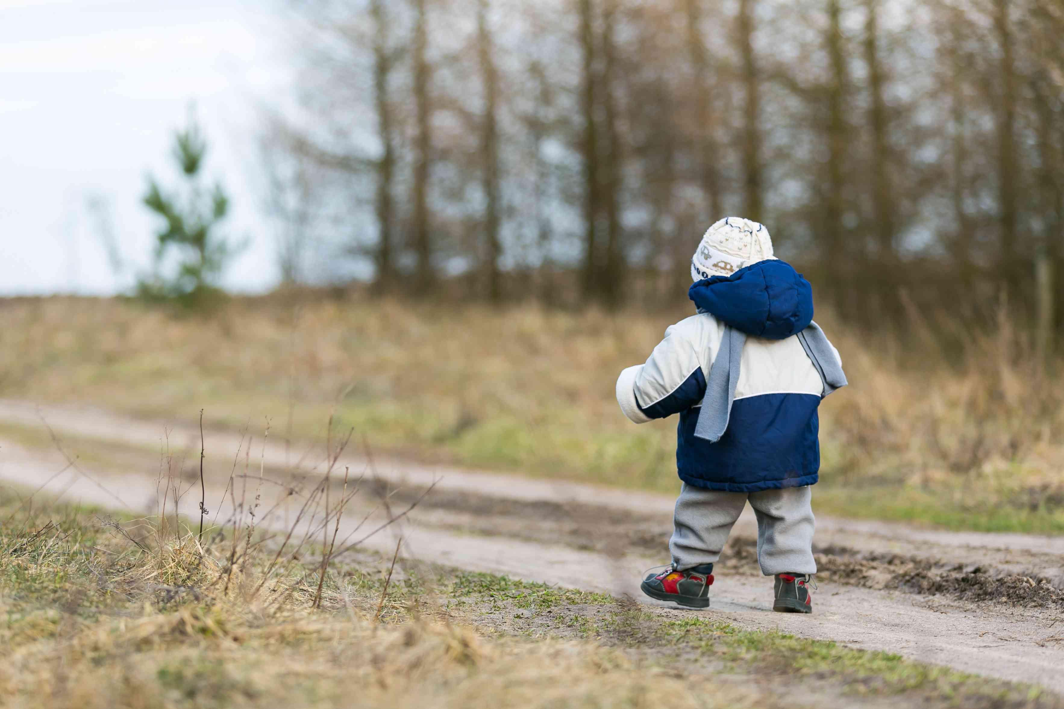 small child walks on rural sandy road