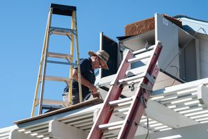 A man installing an evaporative cooler on a roof.