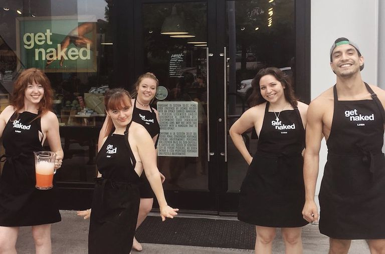 Lush employees stand outside naked with aprons on.