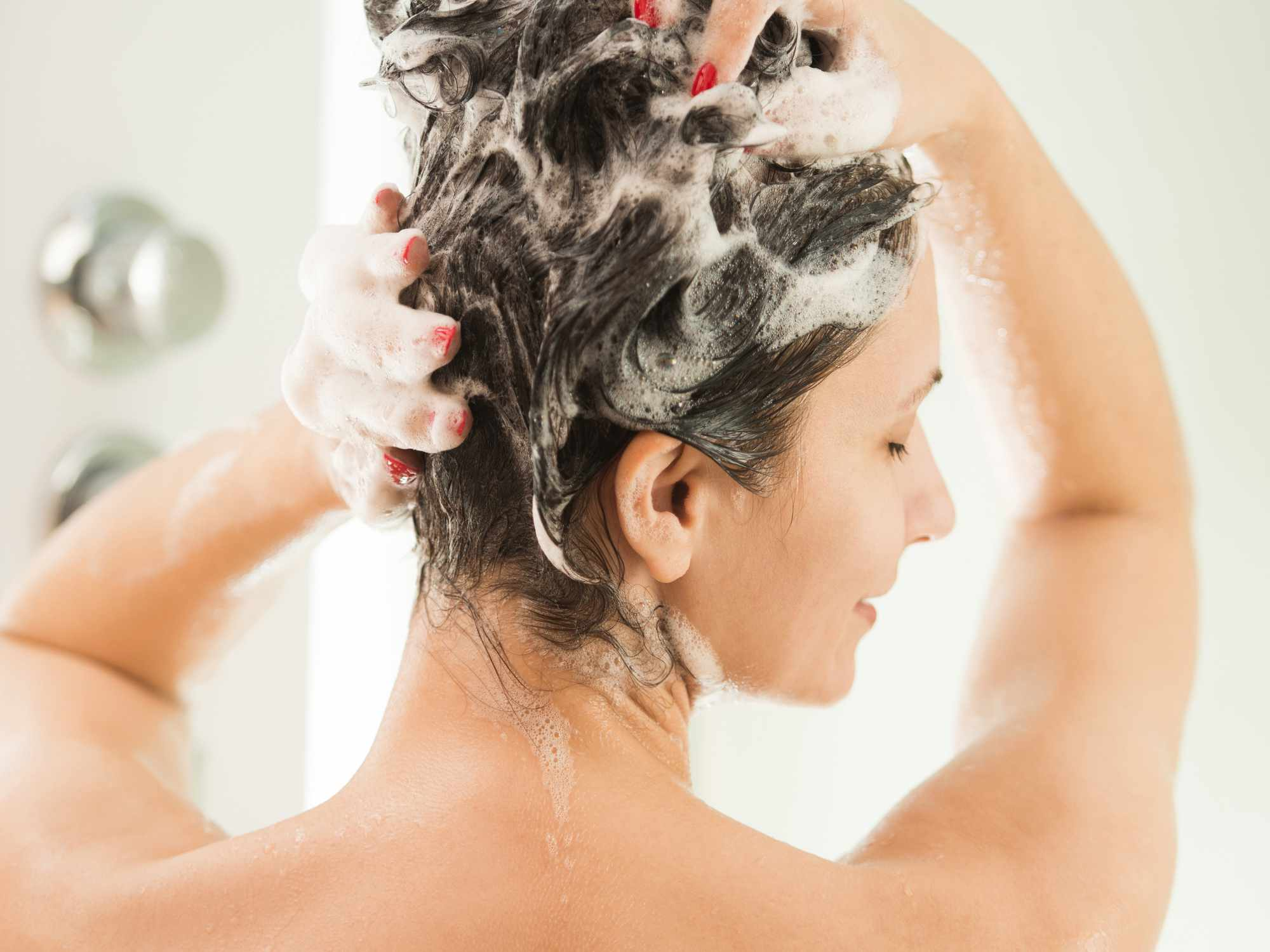 A woman with red nails lathering shampoo in her hair in the shower.