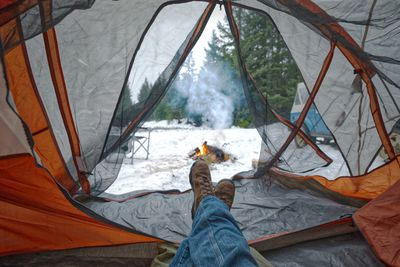 inside view of person camping in tent during winter with fire and snow