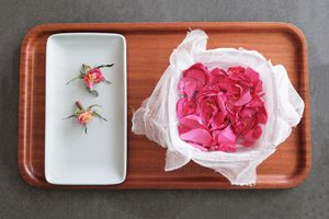 freshly picked pink rose petals in cheesecloth-lined bowl next to white tray with empty buds