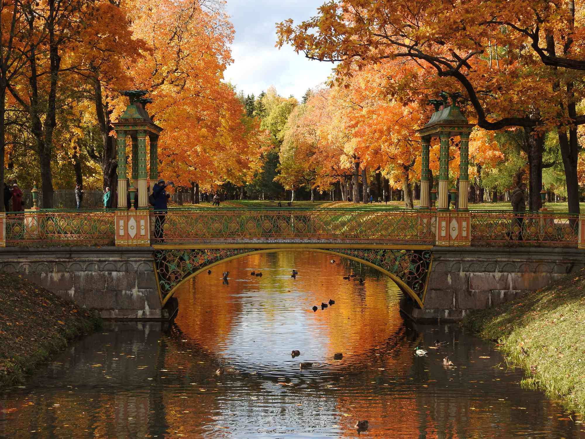 Arch Bridge Over a lake with architectural statues on both sides of the bridge and rows of tall trees in shades of red and orange on both sides of the waterway in St. Petersburg, Russia