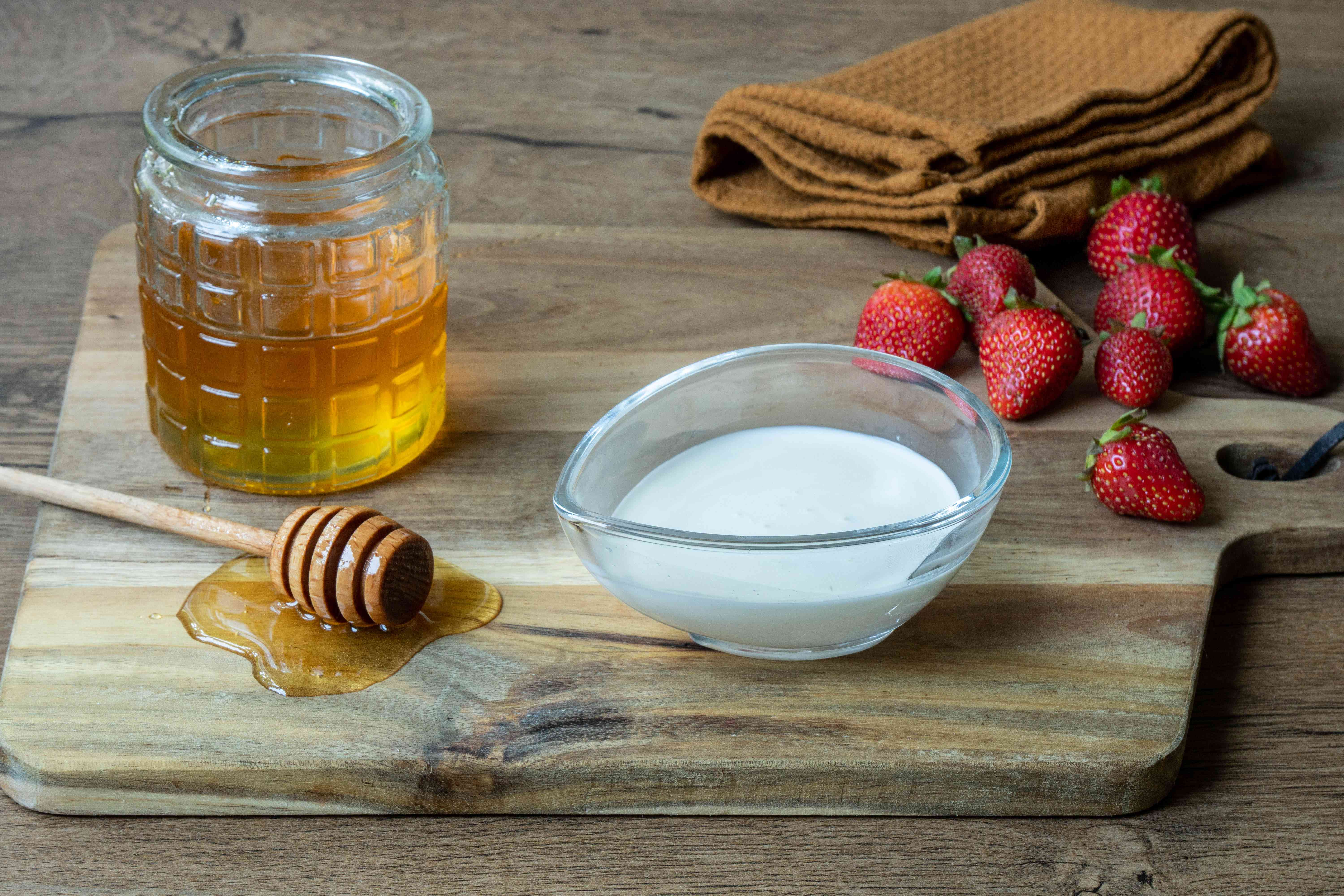glass jar of honey, dipper, heavy cream, and fresh strawberries on wooden cutting board