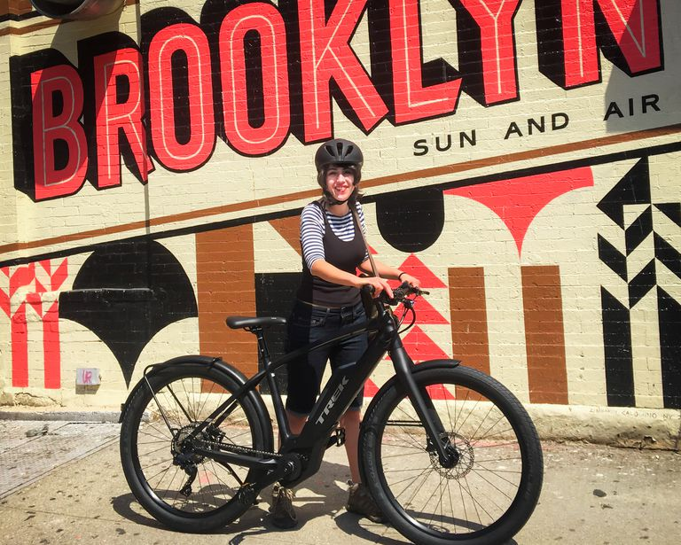 Author posing with ebike in front of a painted brick wall advertising the bike shop