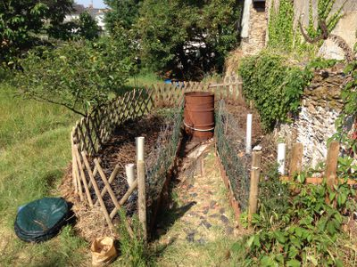 A keyhole garden nestled against a wall