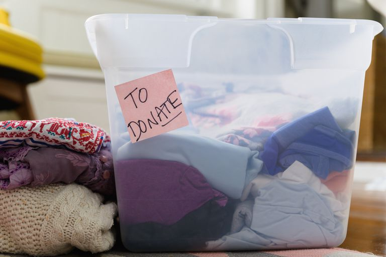 Clothing in a Tupperware bin that will be donated.