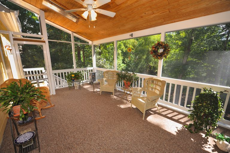 A covered, screened-in porch with a ceiling fan, three chairs, and assorted plants