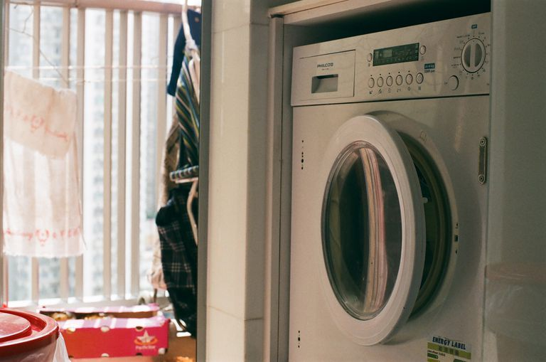 Laundry room with items hanging dry, laundry machine door ajar, and plastic containers