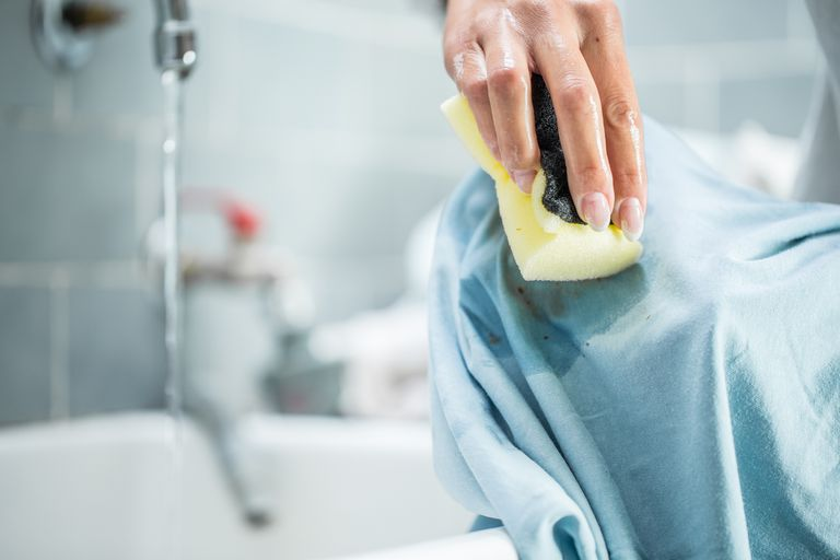 Woman cleaning a stained shirt with a sponge