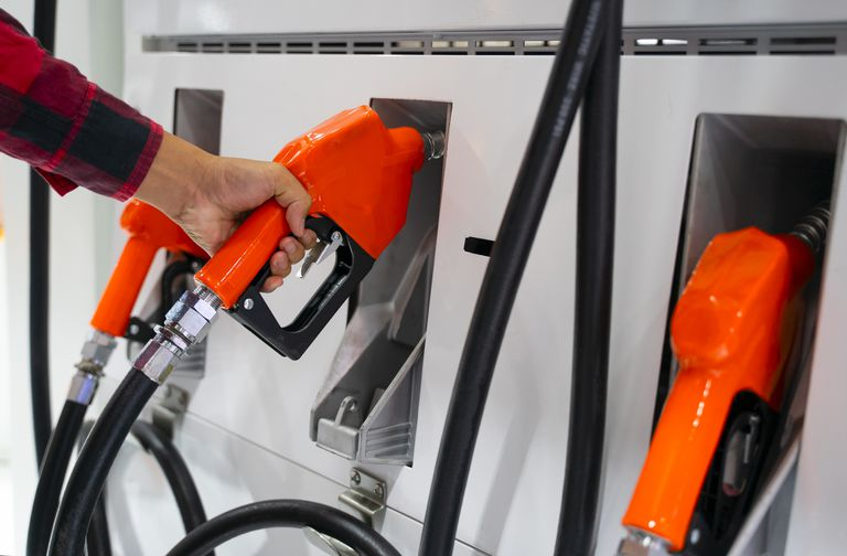 A person holding the nozzle of a biofuel gas pump.