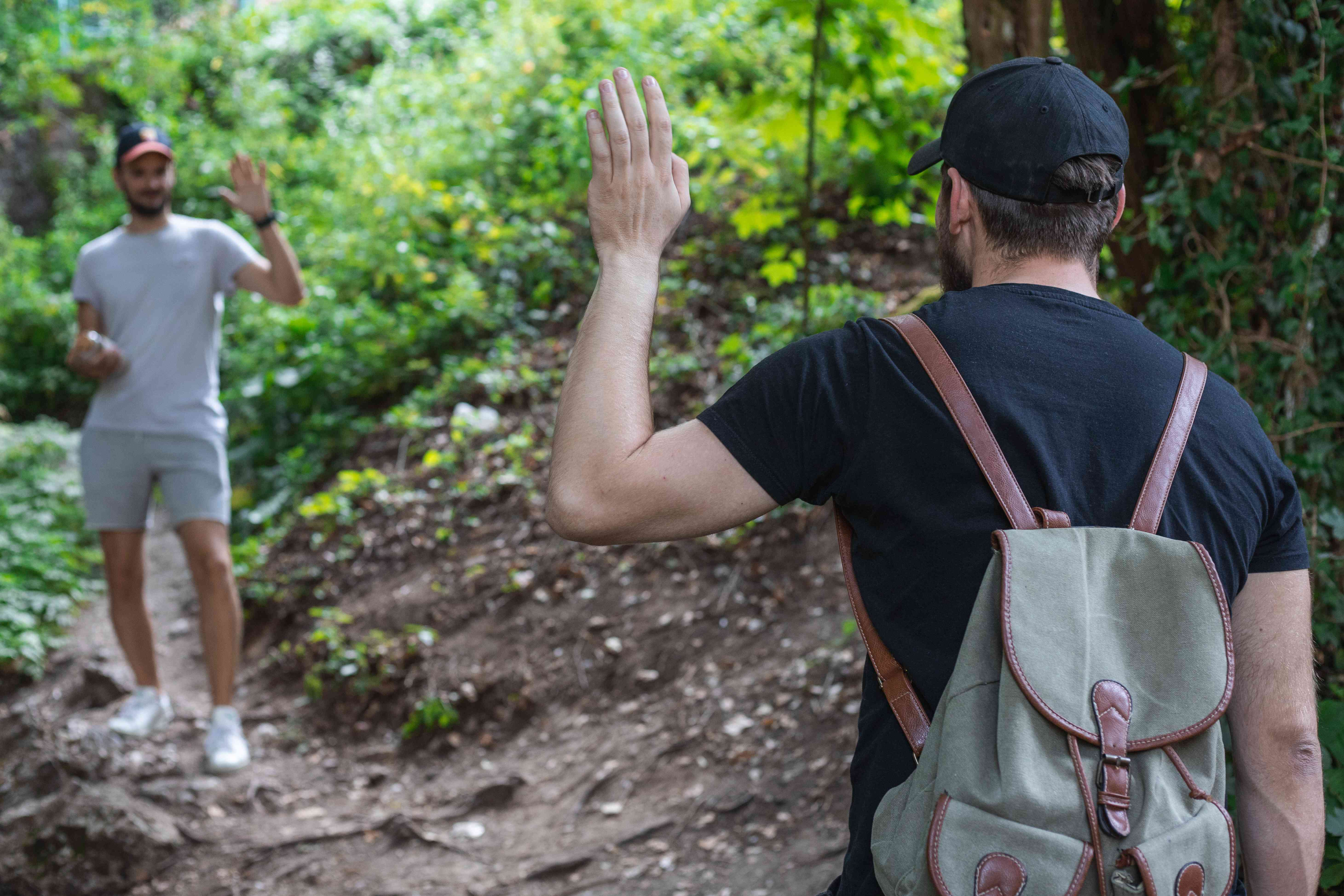 two guys pass each other on hiking trail and wave hello to be friendly