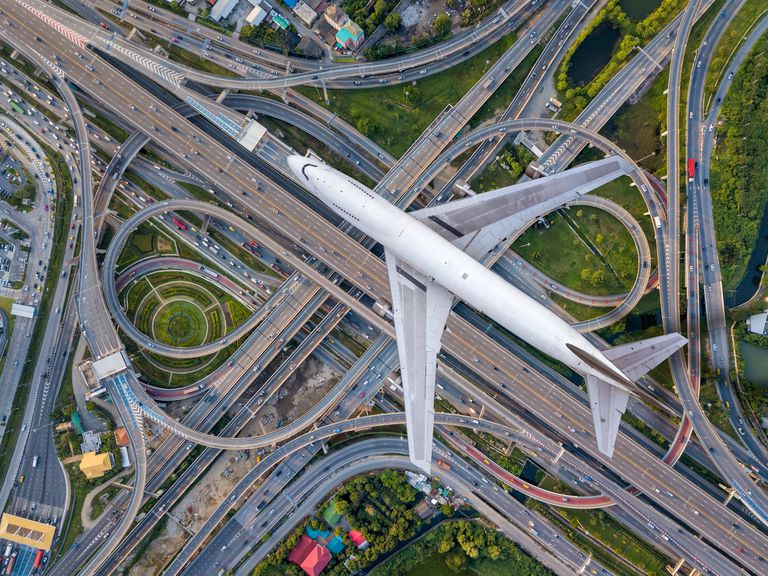 Top view airplane flying over highway road junctions. The Intersecting freeway road overpass the eastern outer ring road of Bangkok, Thailand.