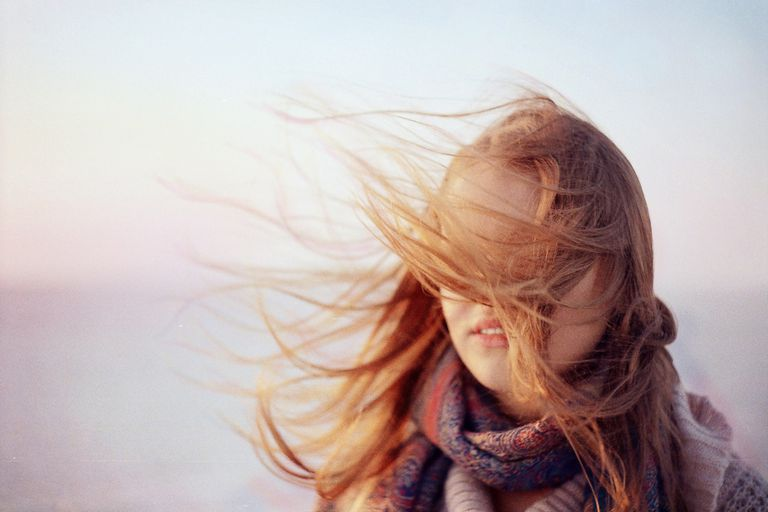 Woman's hair flying in front of her face on a windy day