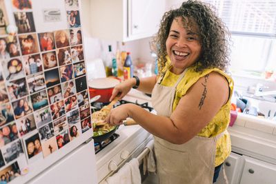 happy woman cooking in her kitchen