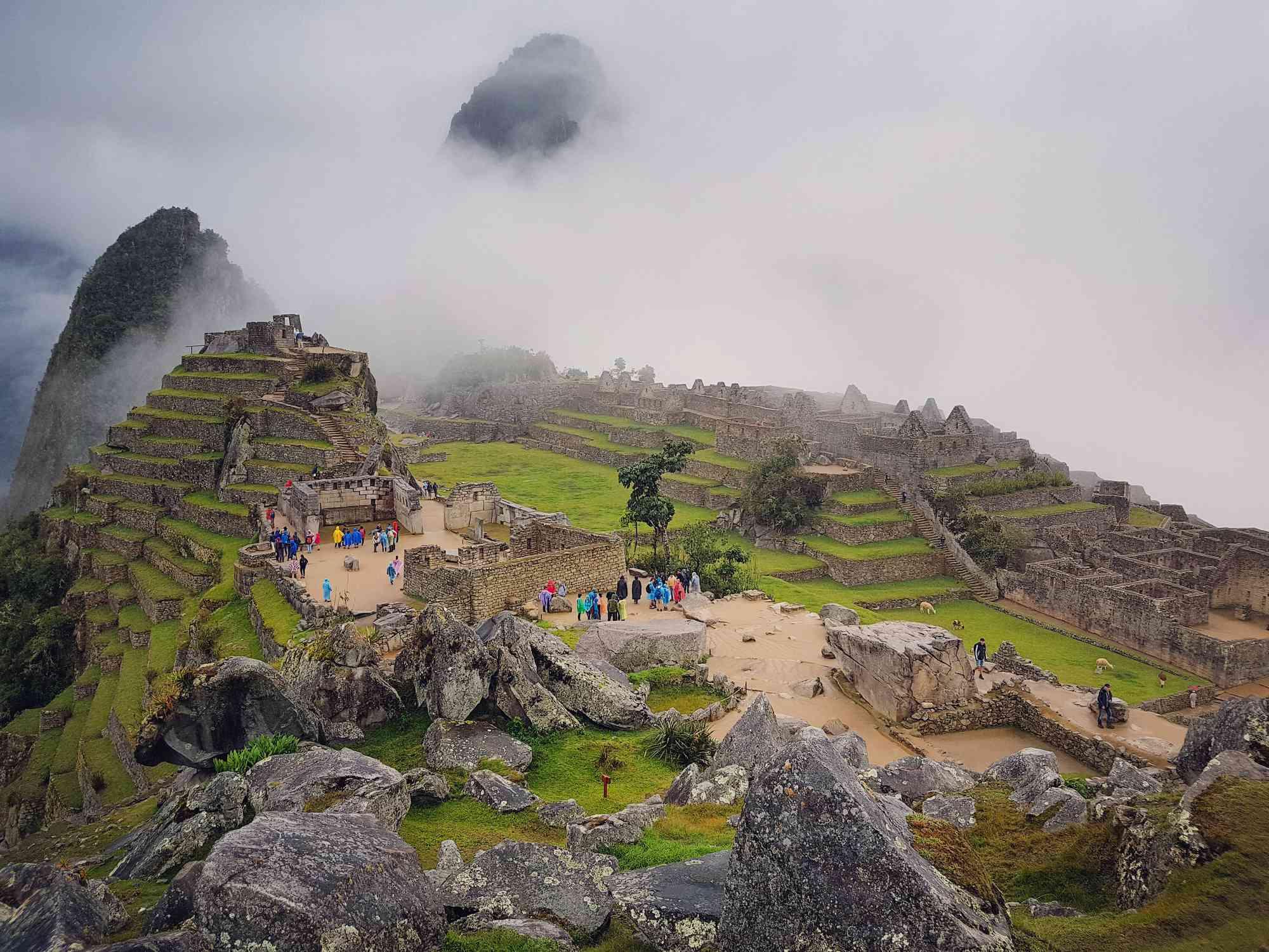 Tourists exploring ruins at Machu Picchu, Peru