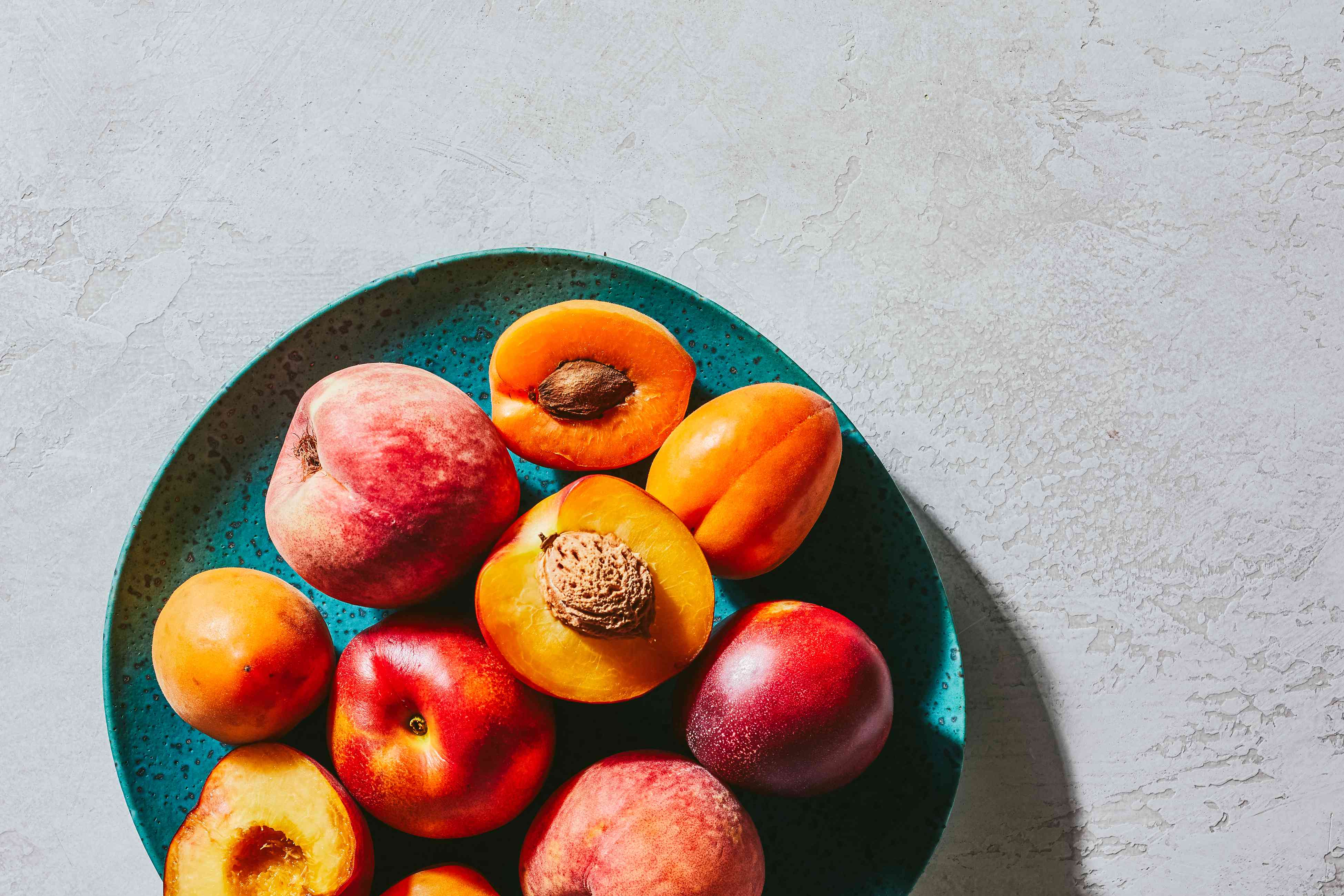 nectarines, peaches, and apricots crowded together onto speckled turquoise plate