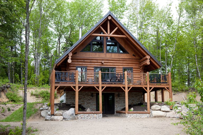 A large log cabin in the woods.