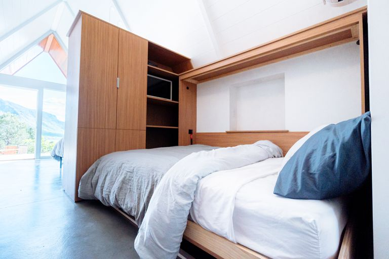 A Murphy bed in a bright sunlit room with large windows.