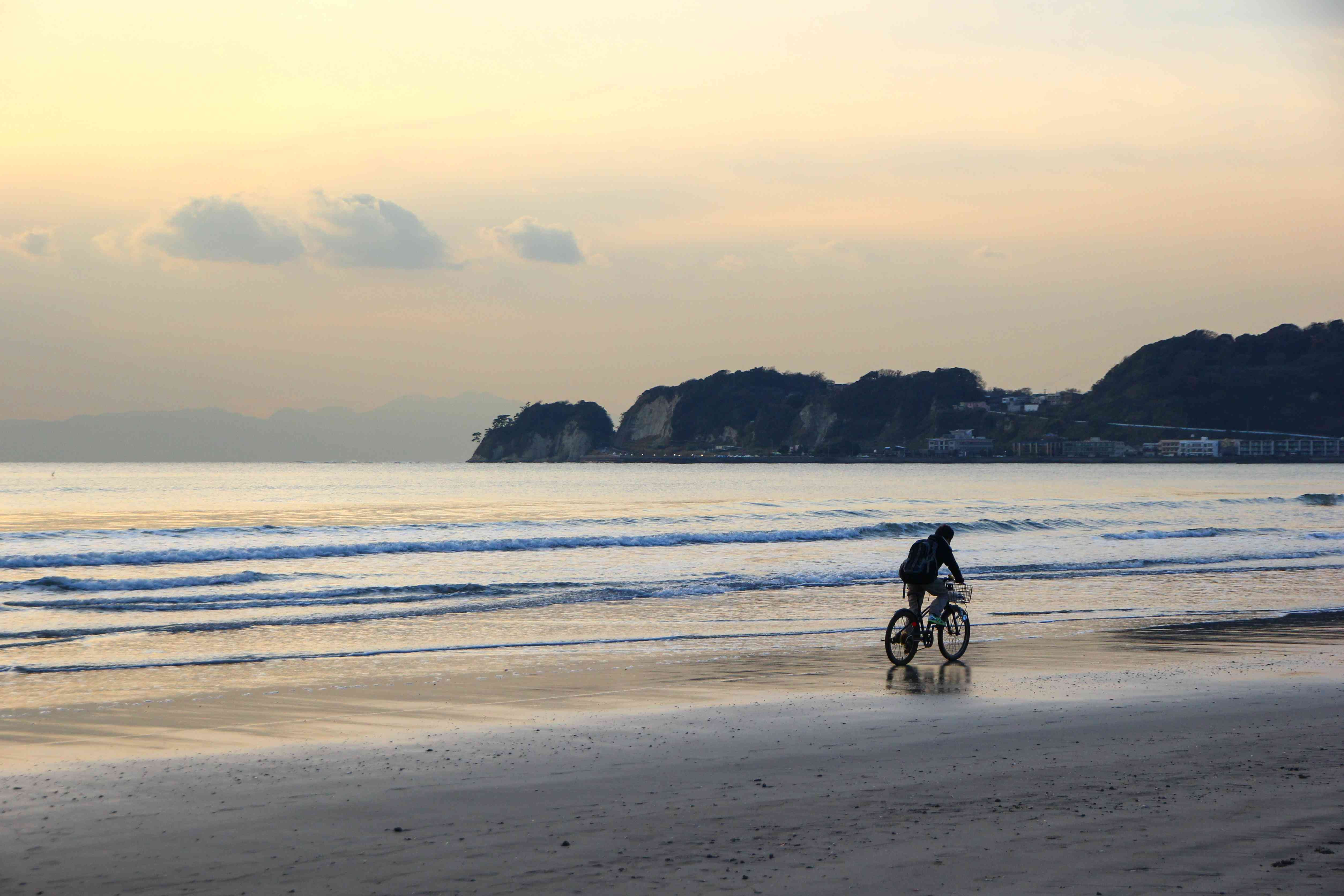 person rides bike along ocean's edge at dusk with hill formation in background