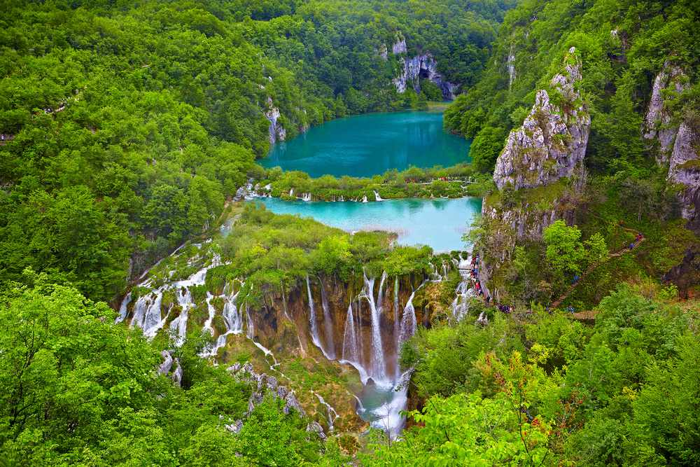 A turquoise blue lake with waterfalls in a forest
