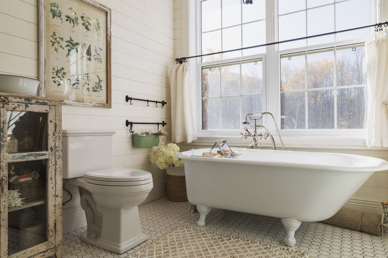 A bathroom with a basin, toilet, big clawfoot tub with natural light.