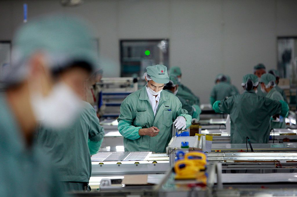 Employees assemble photovoltaic panels at Suntech Power Holdings Co.'s factory in Wuxi, Jiangsu Province, China.