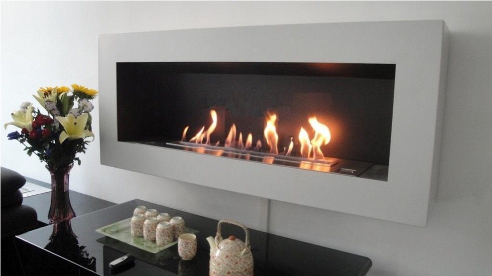 A rectangular fireplace, with a black modern table in the foreground