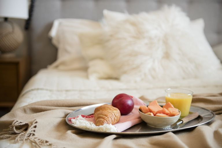 Tray sitting on the end of a bed with a croissant, plum, bowl of cantaloupe, and glass of orange juice