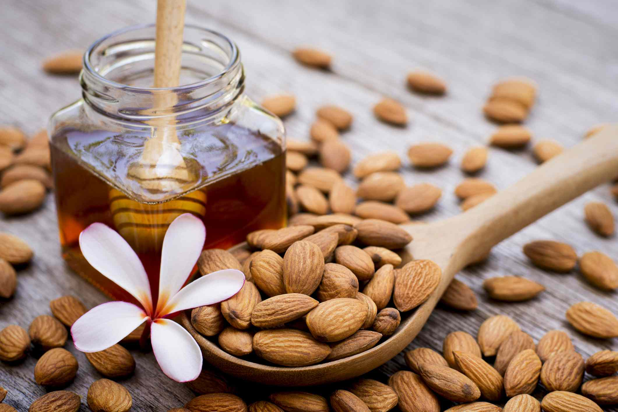 Closeup almond nuts in wooden spoon and pure gold honey in glass jar isolated on wood table background