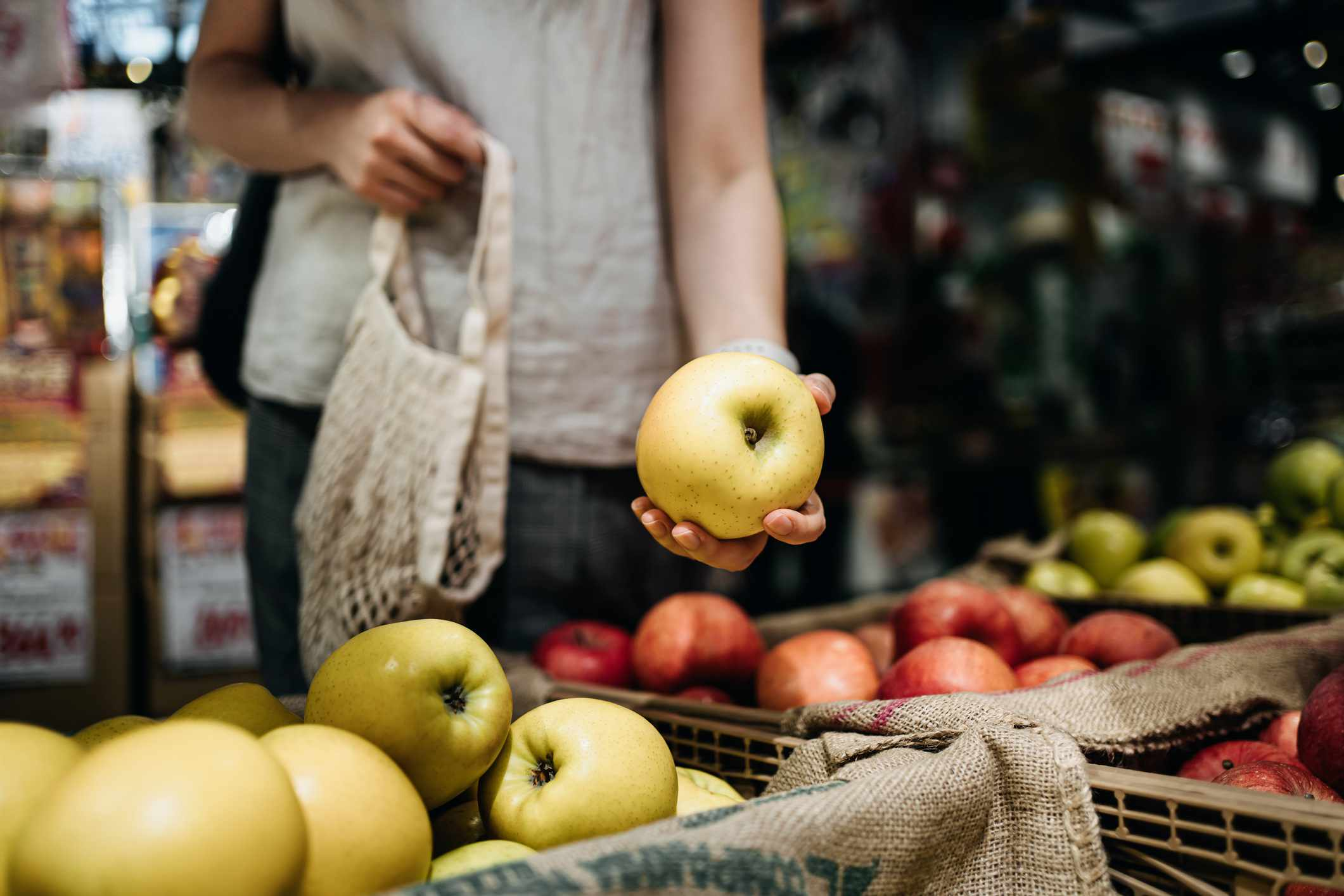A woman picking up an apple at a store.