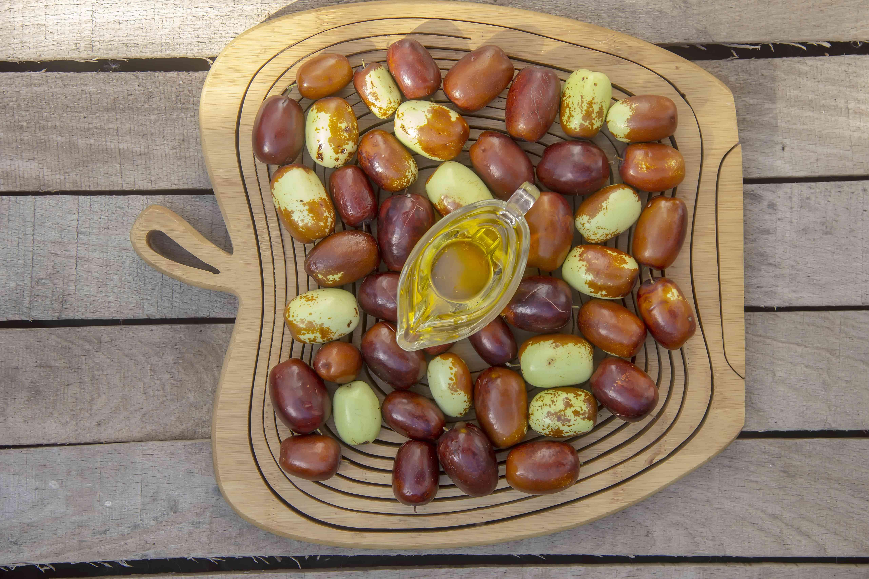 Jojoba fruit and oil on a wood table setting.