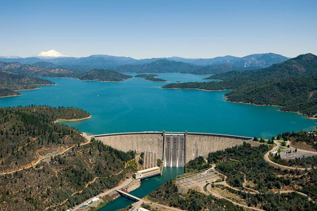The Shasta Dam holds back the greenish-blue waters of the Sacramento River on a bright day