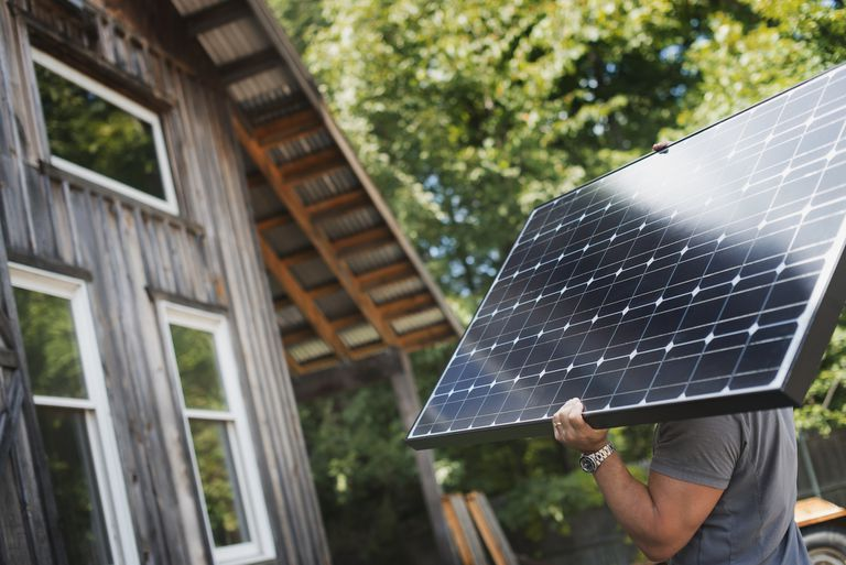 Man carrying solar panel toward a cabin