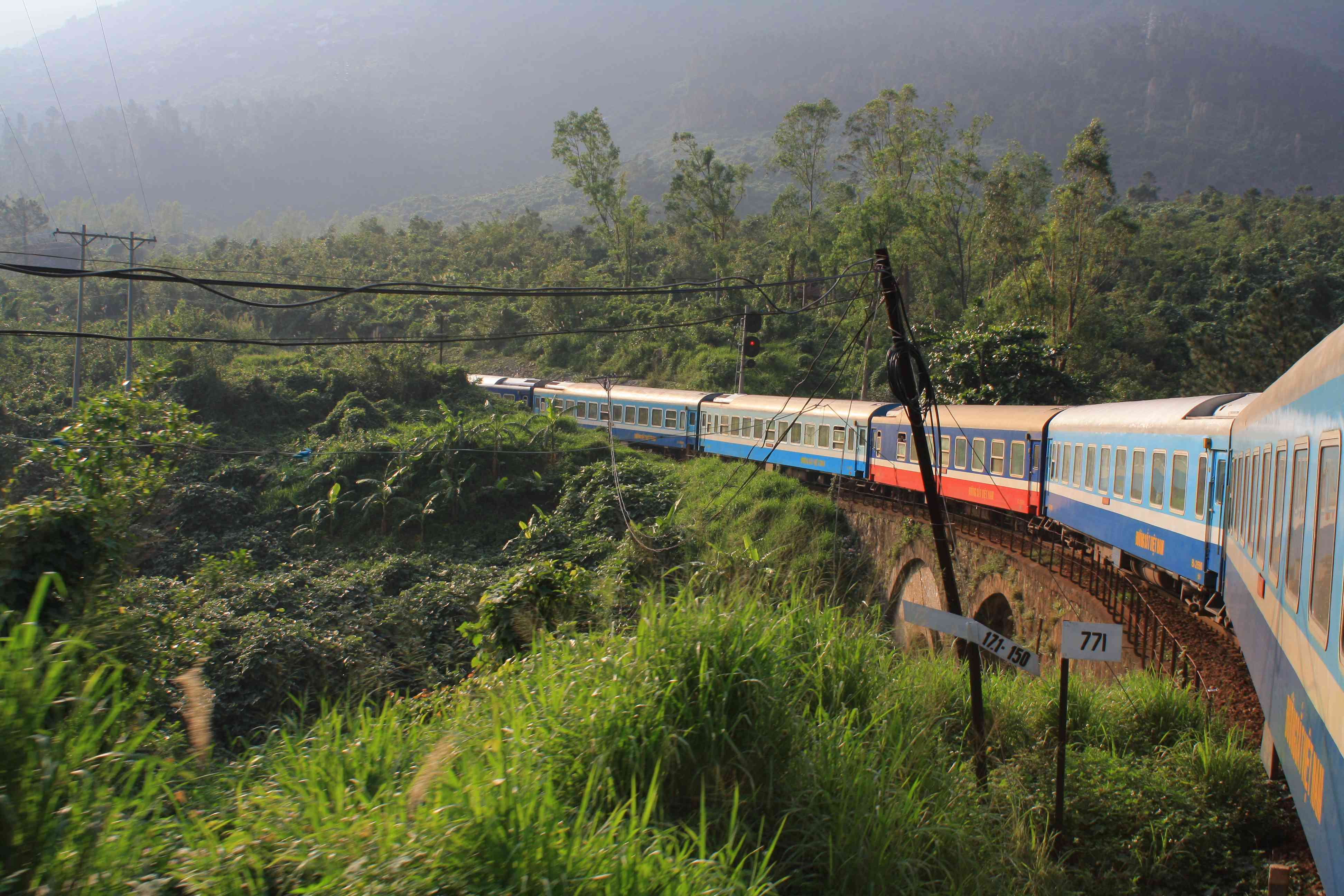 View from train of colorful cars cutting through the jungle