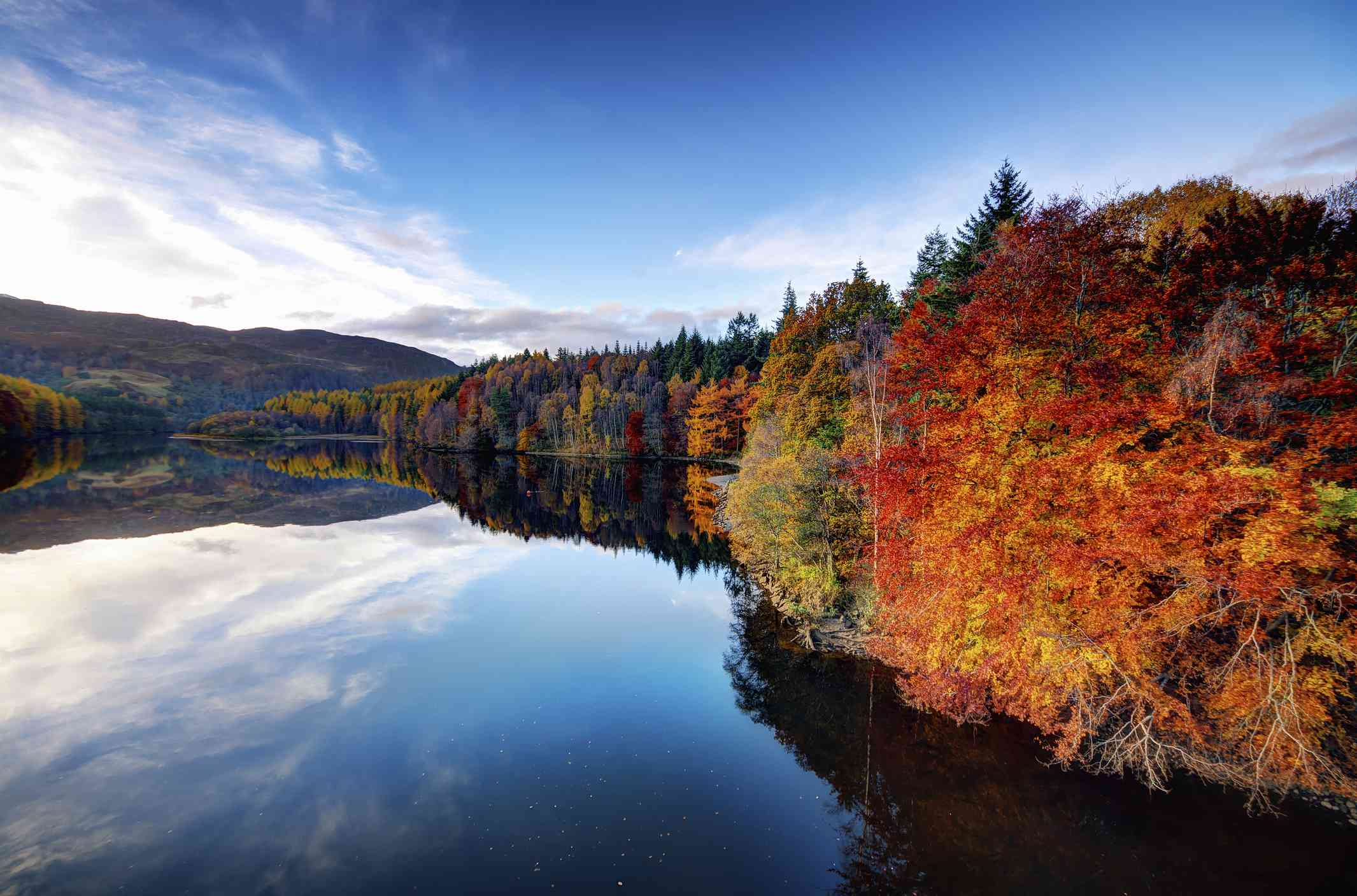 View of Loch Faskally lined with autumn trees in shades of red, gold, and green with a blue sky and white clouds above reflected in the lake
