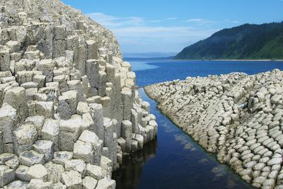 White basalt columns submerged in sea at Cape Stolbchatiy, Russia