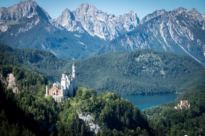 Aerial view of Neuschwanstein Castle surrounded by mountains and lush, green foliage