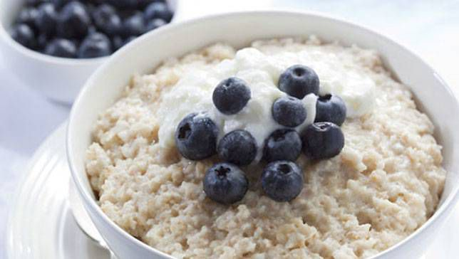 bowl of oatmeal with blueberries on top and on the side