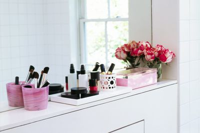 Makeup organized in pink containers on a bathroom ledge with a vase of pink tulips in the corner