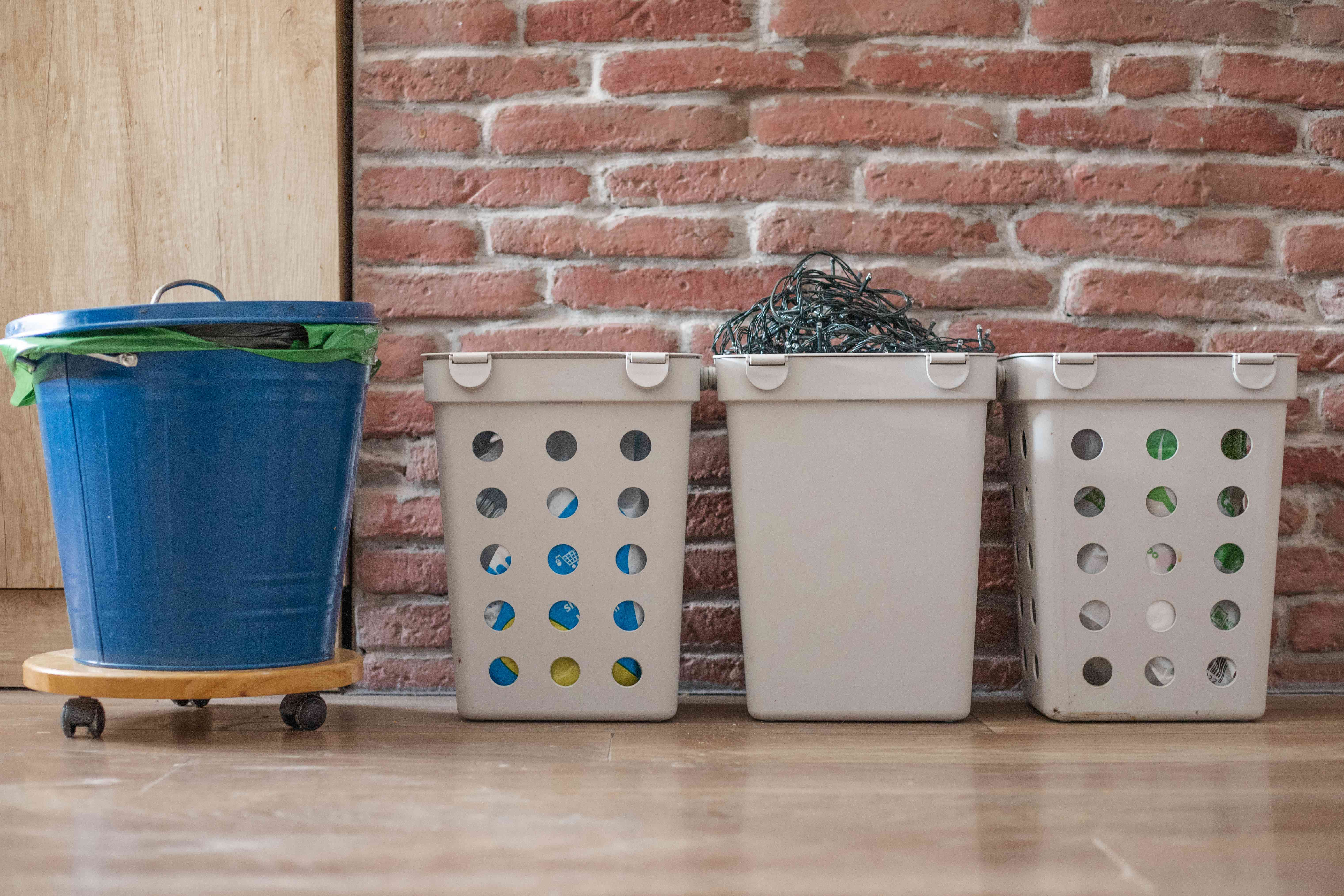various trash bins including gray plastic container filled with dead christmas lights