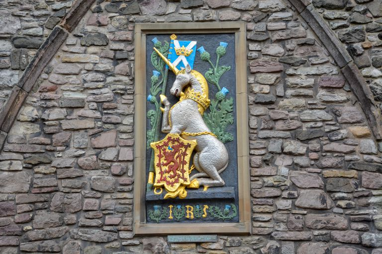 Unicorn with the Scottish flag and an emblem with a red lion on gold on a stone wall