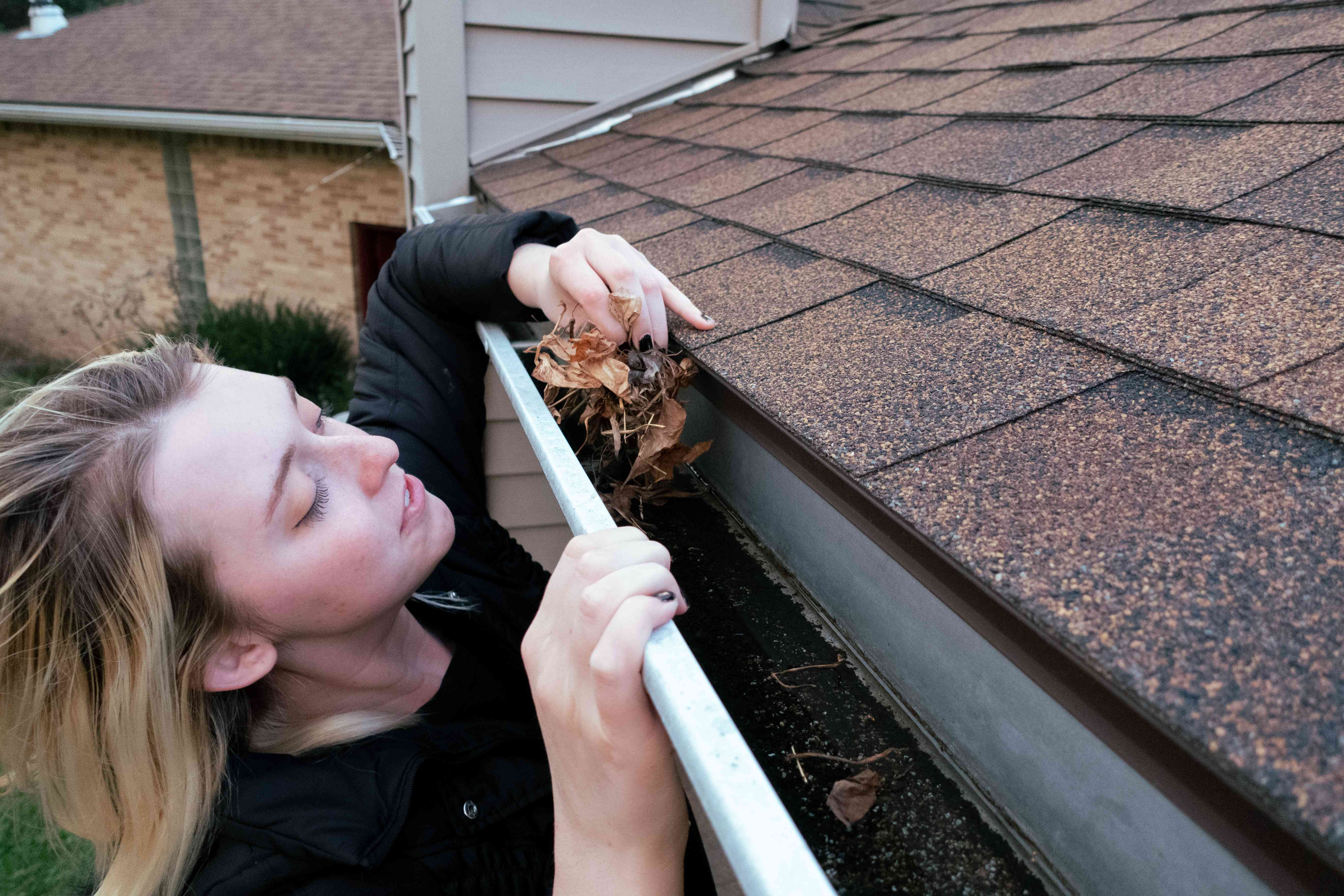woman cleans gutters from house full of wet leaves