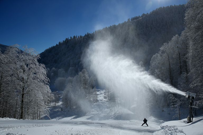 A snow machine in Sochi spitting out snow on mountain.