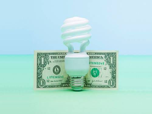 Twisting light bulb and dollar bill on a blue and green background