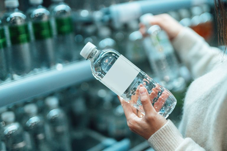 A woman holding bottled water in a store.