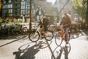 Two men riding bikes near a canal in Amsterdam