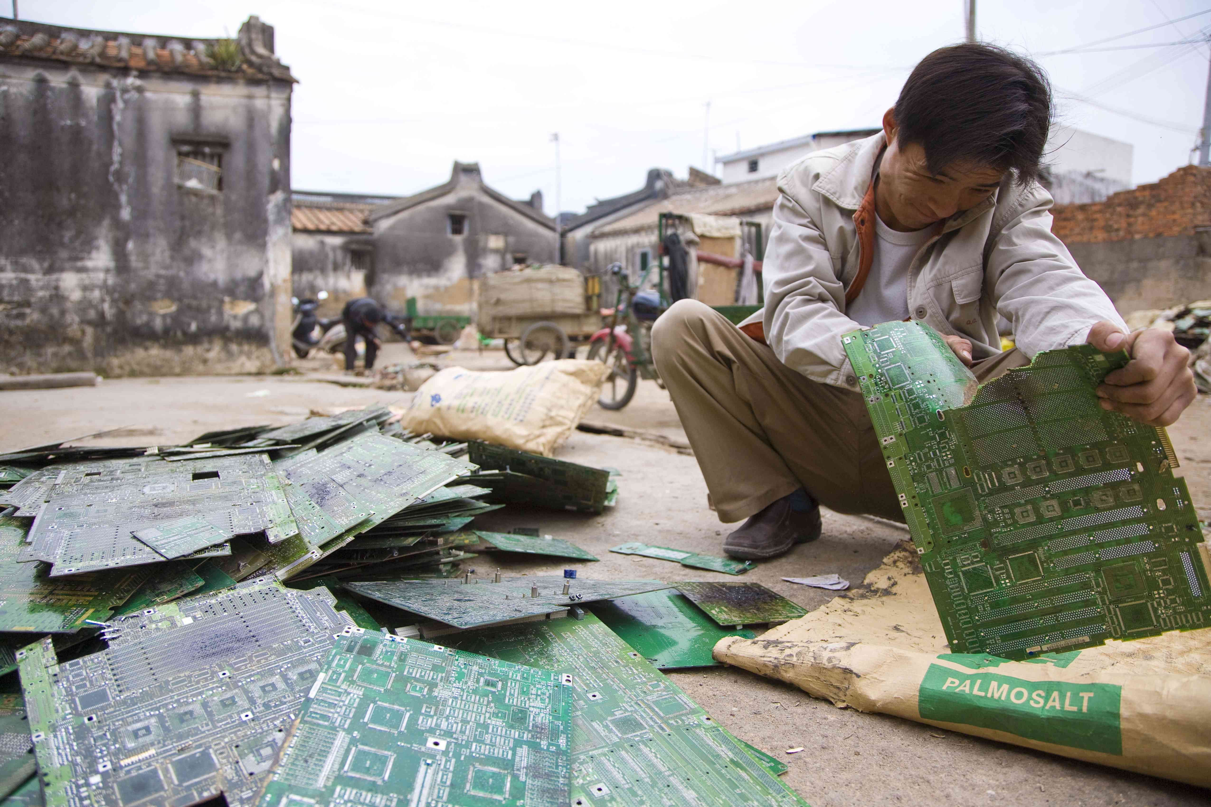 A man strips e-waste outside in China.